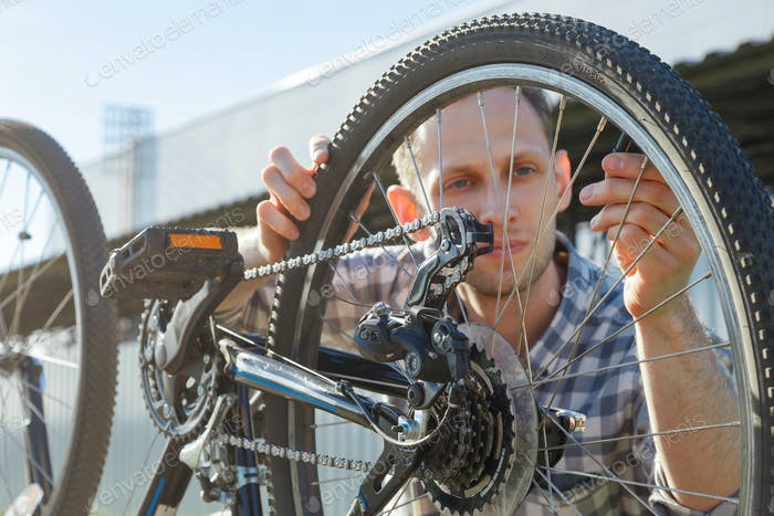 A young male engineer master is looking at a bicycle wheel