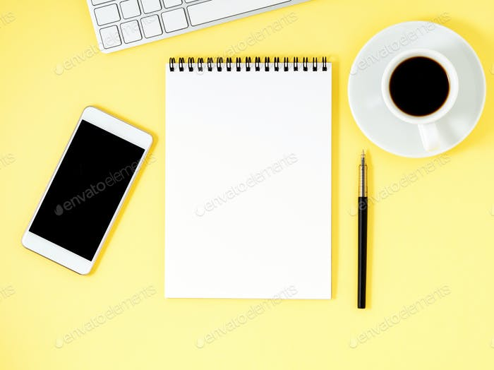 Top view of yellow office desktop with notepad, computer keyboard, smartphone. Mock up, empty space