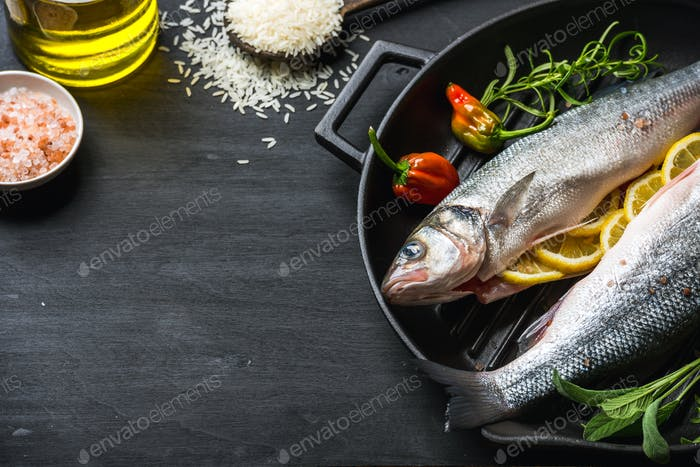 Raw uncooked seabass fish with herbs