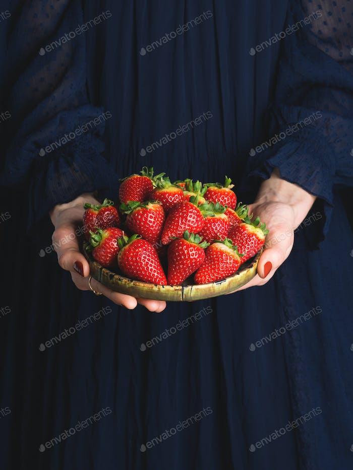 Gericht von Erdbeeren in den Händen einer Frau