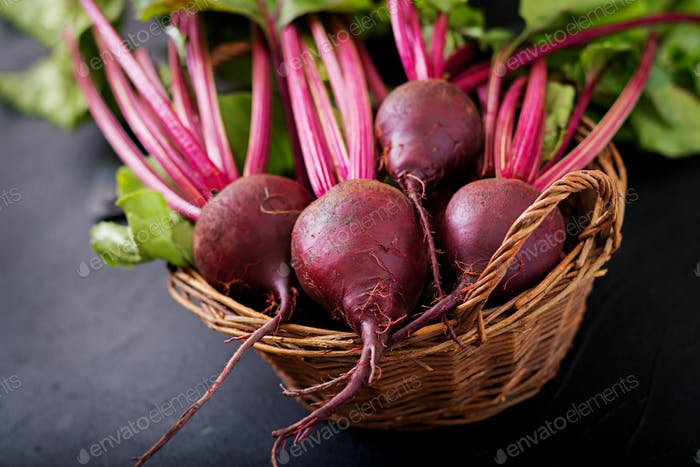 Young beetroot with a tops in a basket on a dark background.