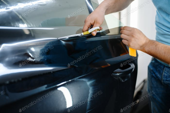 Male wrapper holds sunscreen film, car tinting