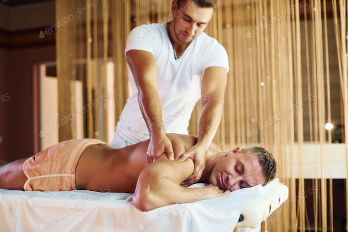 Man does massage to the guy in that lying down in cabinet indoors