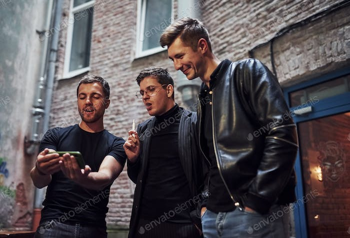 Three male friends stands outside the bar. Having conversation. In nice clothes