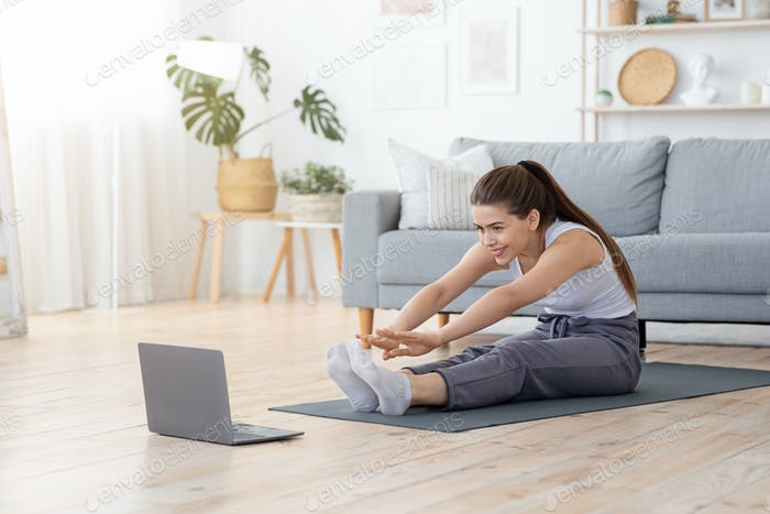 Flexible girl stretching body at home, watching videos on laptop