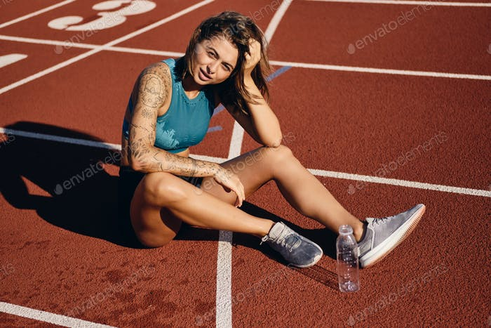 Athlete girl in wet sportswear tiredly looking in camera resting after running on city stadium