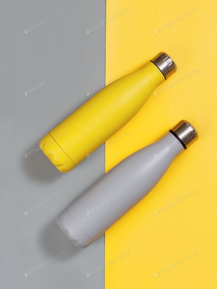 Placeit - Grey and yellow reusable insulated bottles on grey and yellow background