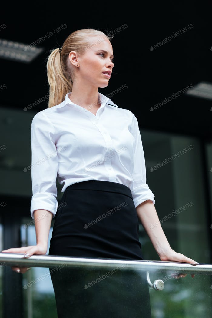 Beautiful blonde businesswoman leaning on the glass railing