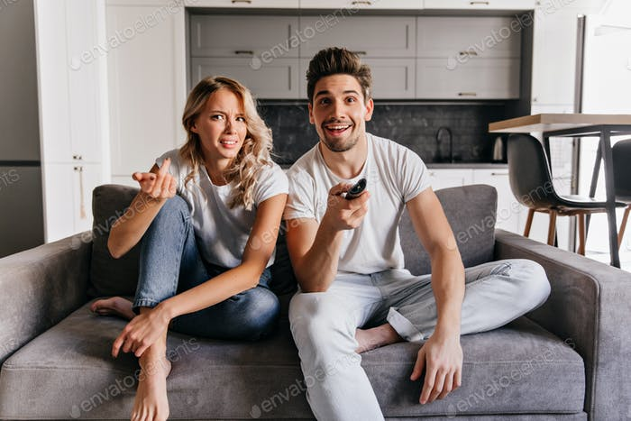 Barefooted lady in jeans watching TV. Indoor photo of couple relaxing on grey sofa