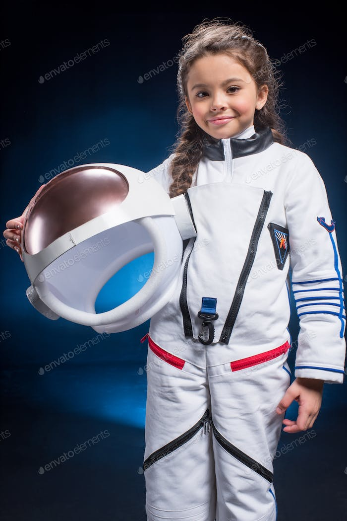 Little girl in space suit holding helmet  and smiling at camera