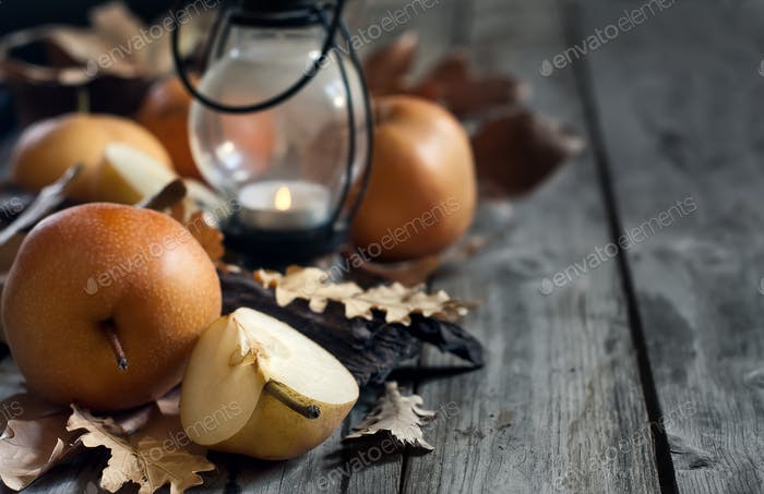 Asian pears, lantern and fall leaves background