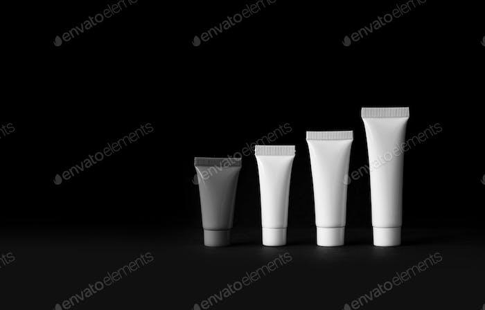 Kosmetik-Röhren auf schwarzem Hintergrund gesetzt.