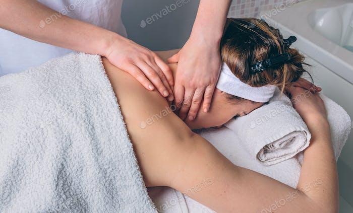 Mujer que recibe masaje en el cuello en el centro clínico