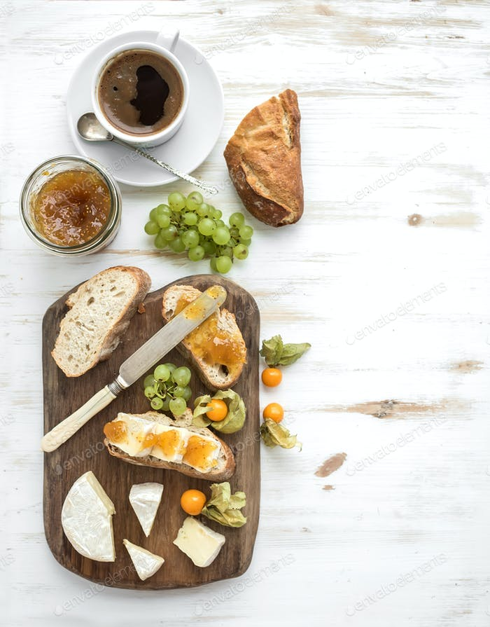 Breakfast set. Brie cheese and fig jam sandwiches with fresh grapes, ground cherries