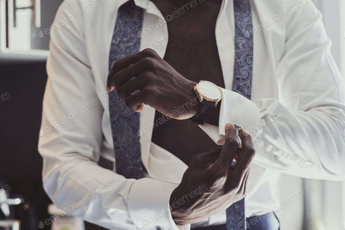Elegant man is dressing up his cufflinks