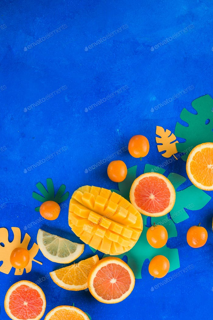 Tropic fruits on a vibrant blue background with copy space. Mango, oranges, kumquat, and other