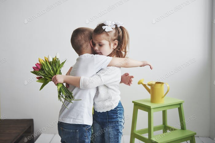 Beautiful boy and girl with tulips with embrace. Mother's Day, 8 March, a happy birthday