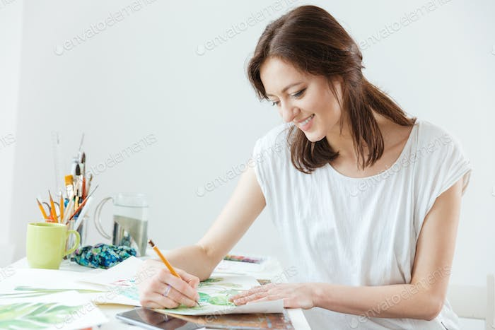 Woman painter drawing at the table