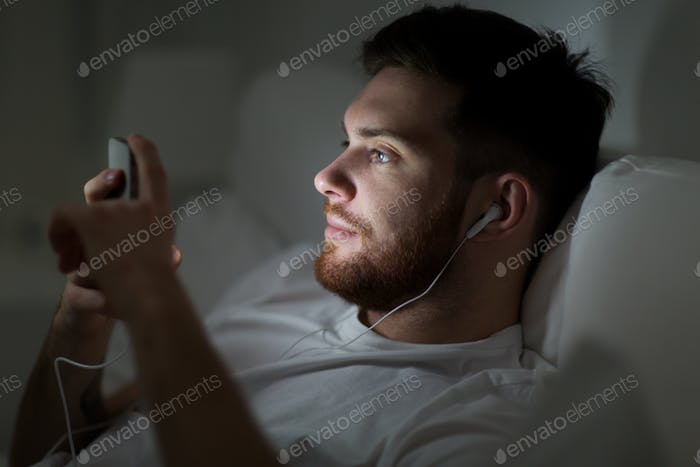 man with smartphone and earphones in bed at night