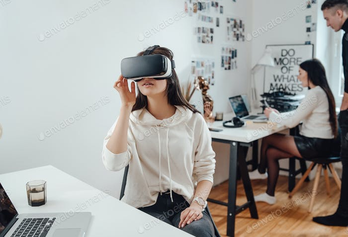 Female business person wears virtual reality headset in office