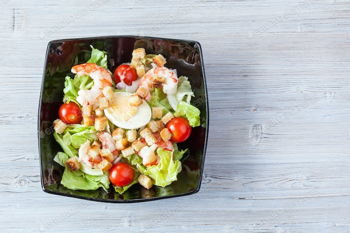 top view of Caesar salad with prawns in black bowl