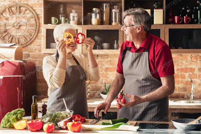 Positive senior couple having fun on kitchen