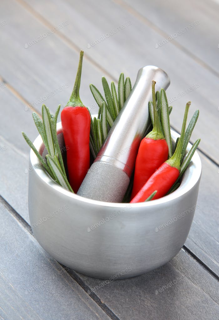 Fresh rosemary herb and red pepper in metal mortar with pestle