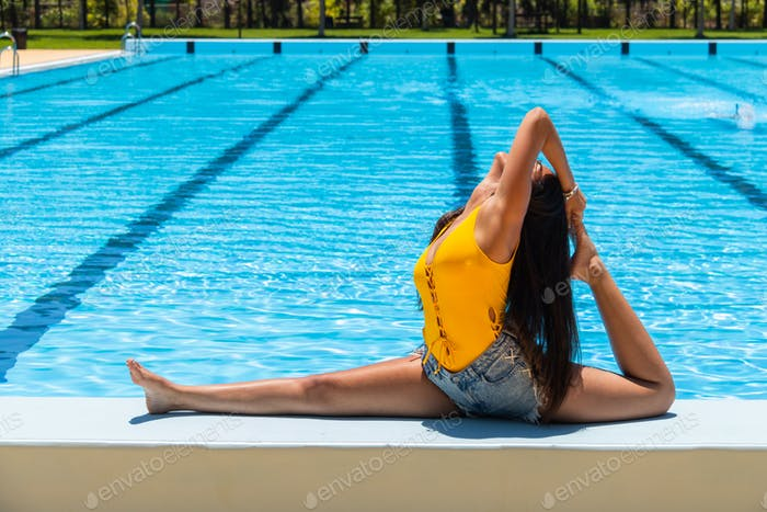 One girl practicing ballet at the swimming pool.