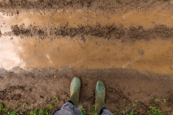 Farmer in rubber boots standing on muddy dirt road
