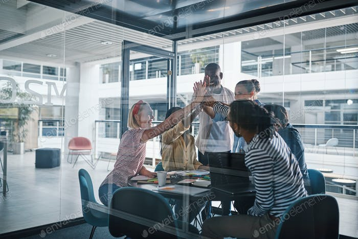 Diverse businesspeople laughing and high fiving together in a boardroom