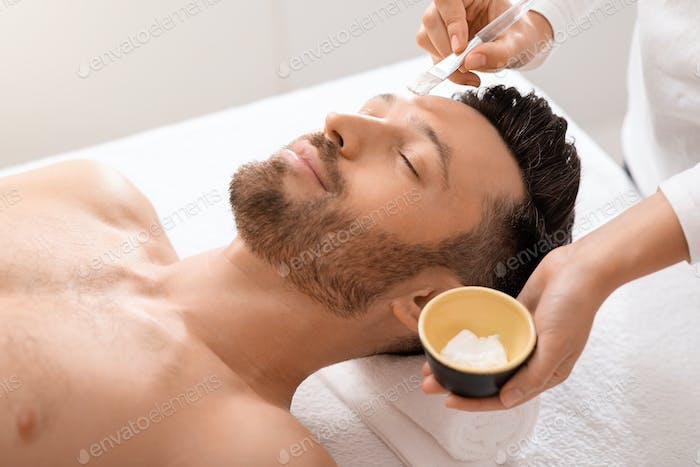 Relaxed man attending cosmetologist or spa salon