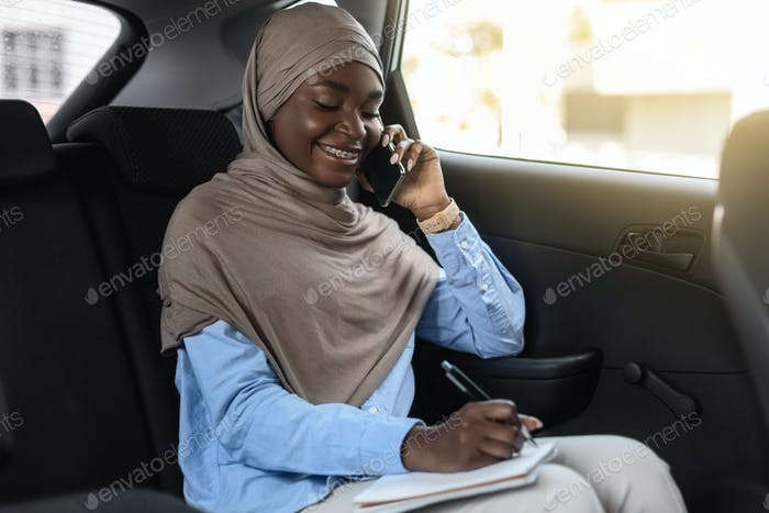 Smiling Black Islamic Businesswoman Taking Notes And Talking On Cellphone In Car