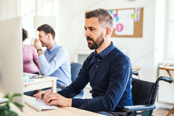 Young businessman in wheelchair with colleagues working in a modern office.