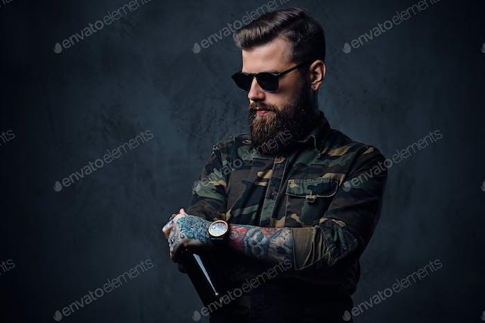 Ein Mann, der in Militärhemd gekleidet ist, trinkt Craft Bier.