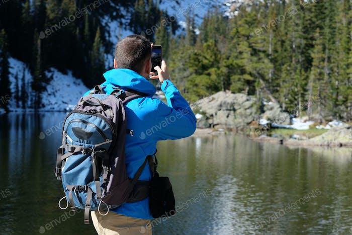 Rucksackpacker fotografiert mit Smartphone