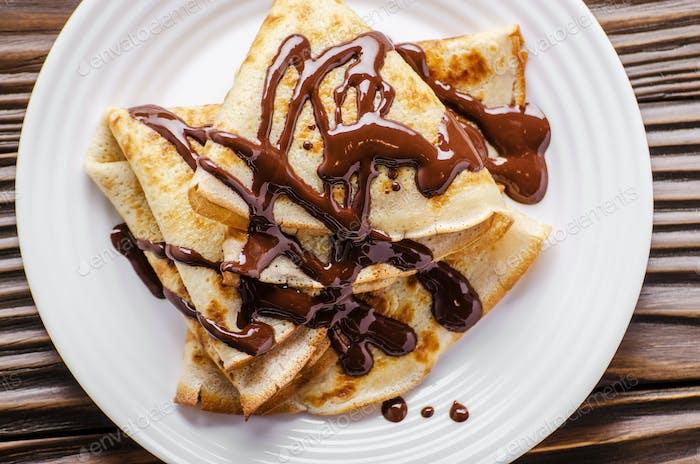 Flache französische Crepes mit Schokoladensauce in Keramikschale auf Holzküchentisch