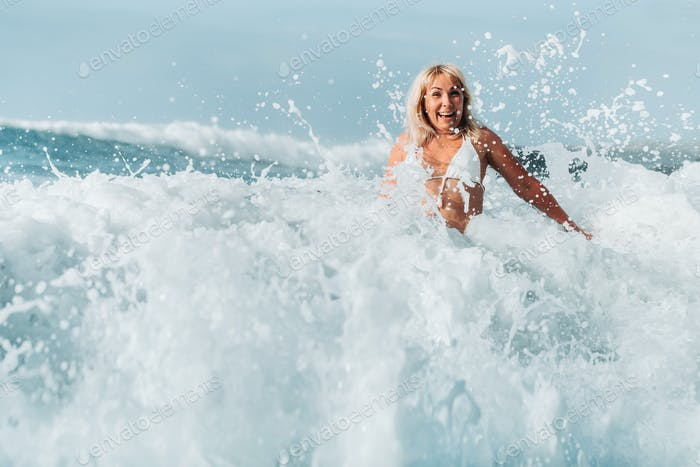 A girl with wet hair jumps over large waves in the Atlantic ocean, around a wave with splashes of