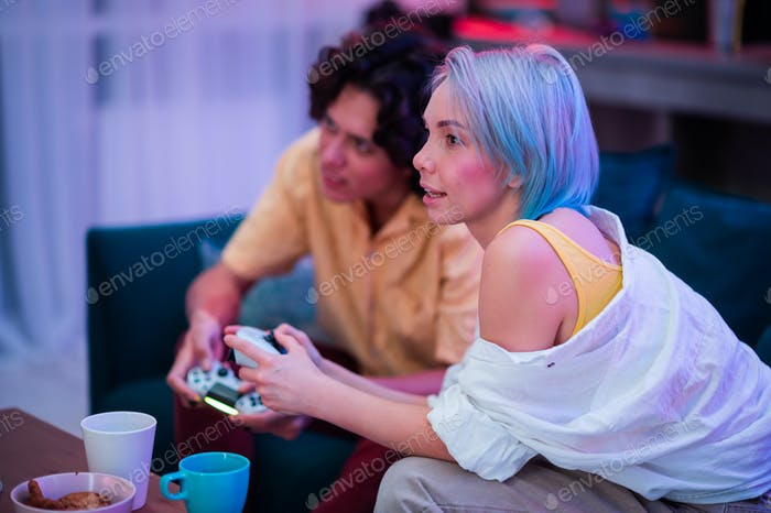 Smiling couple holding gamepads playing video game at home. Young people spending time together