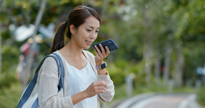 Woman use of mobile phone for sending audio message at outdoor