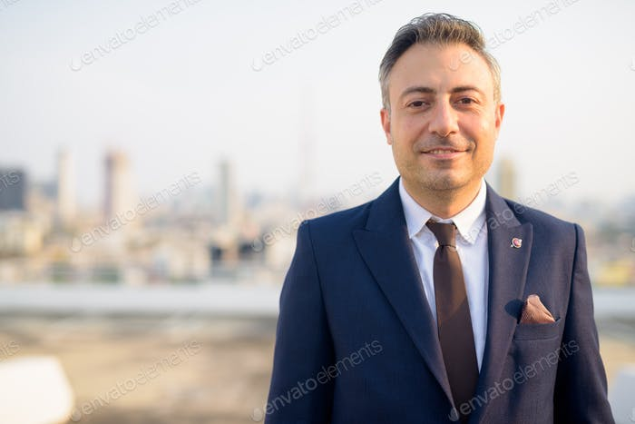 Face of happy mature businessman smiling against view of the city