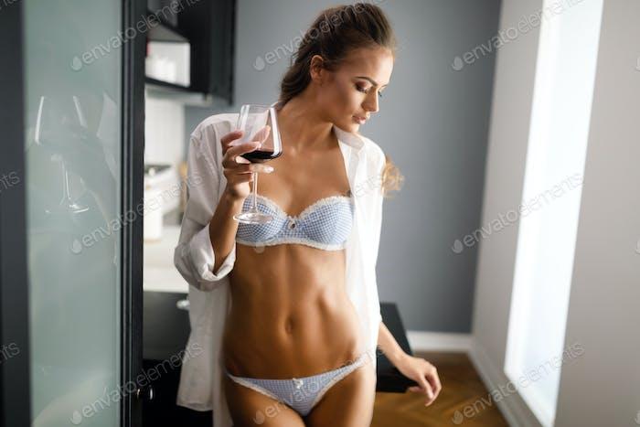 Sexy junge Frau in Dessous trinken Wein zu Hause