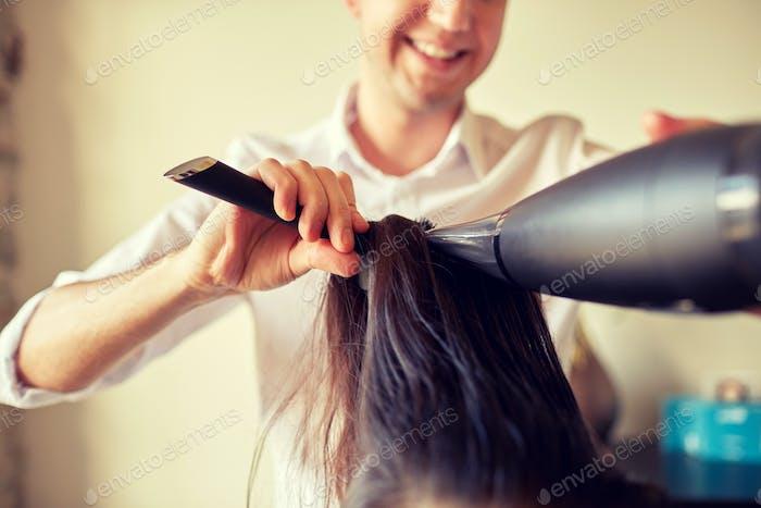 close up of stylist making hairdo at salon