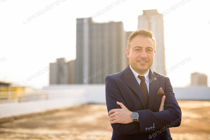 Happy mature handsome businessman in suit against view of the city