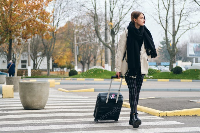 Attractive girl thoughtfully walking on crosswalk with suitcase