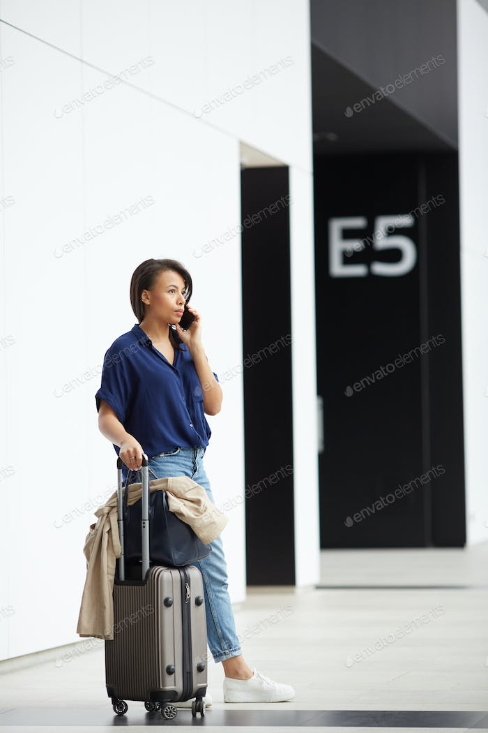 Young woman communicating on phone in airport