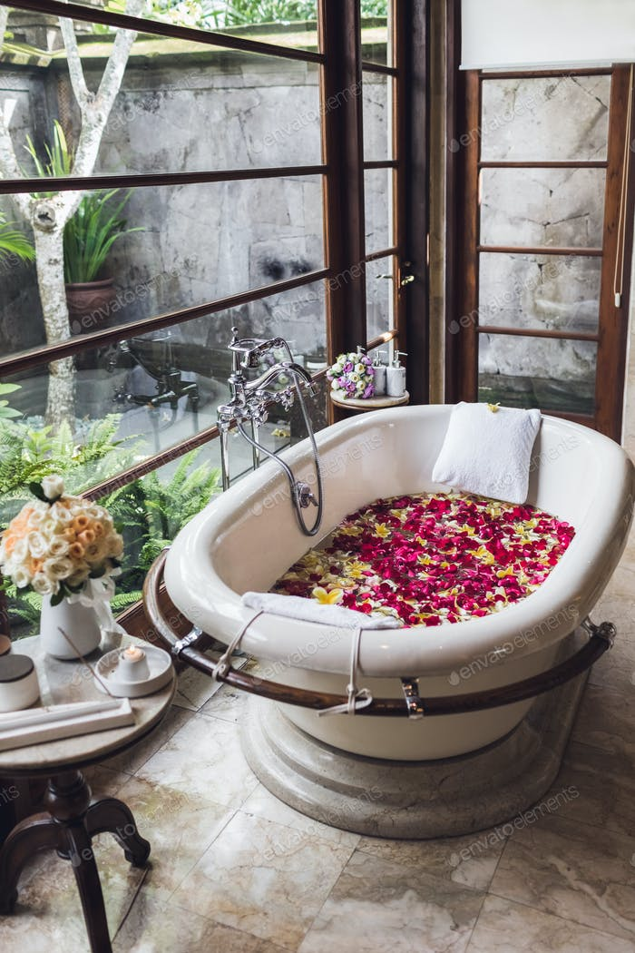 Bath tub with tropical flowers, spa, relaxation, body care, therapy. Top view