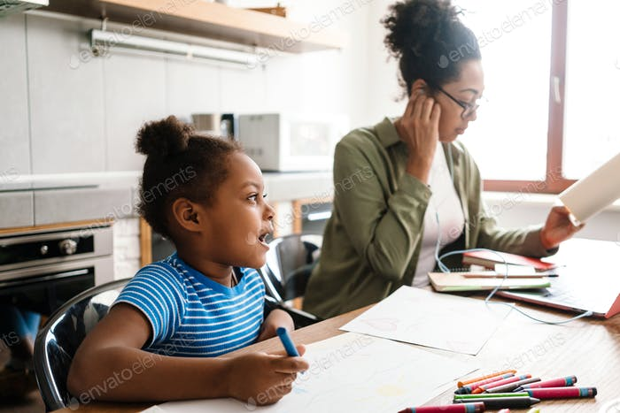 Black woman working while her daughter drawing at home kitchen