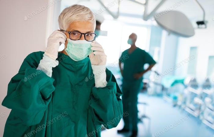 Porträt der weiblichen Chirurgin trägt chirurgische Maske im Operationssaal