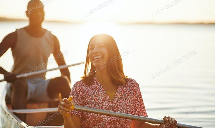 Lachende junge Frau genießen einen Tag Kanufahren mit ihrem Freund