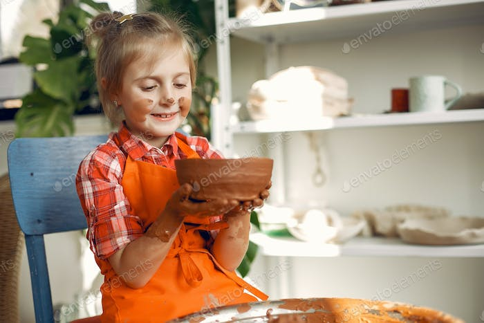 Girl making a vaze from a clay on a pottery's machine